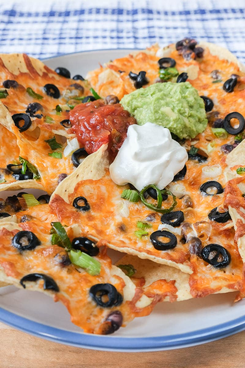 cheesy loaded nachos on large blue plate with towel behind