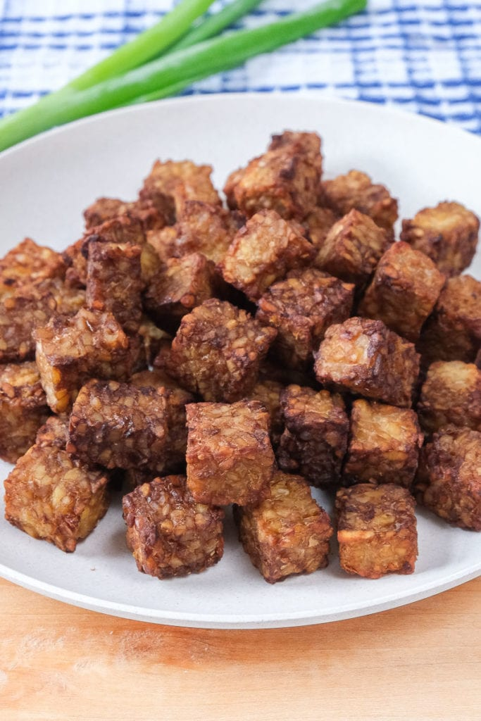 cooked tempeh cubes on white plate on wooden board