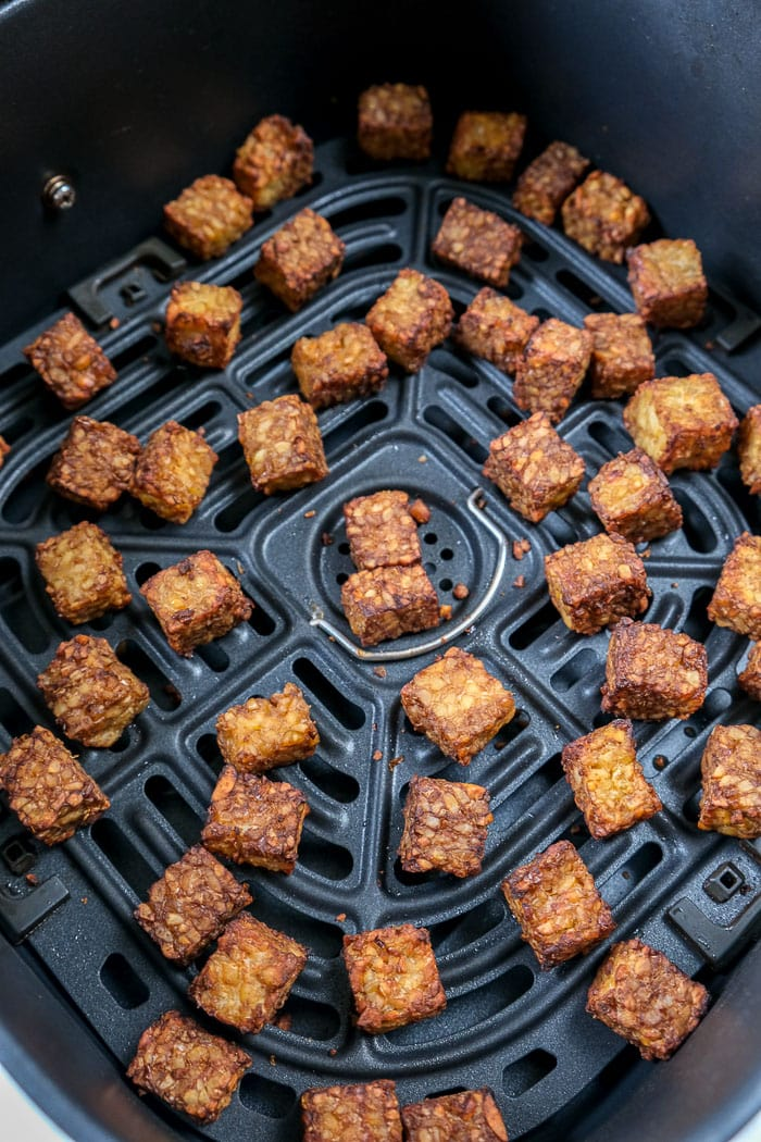 cooked tempeh pieces in black air fryer tray