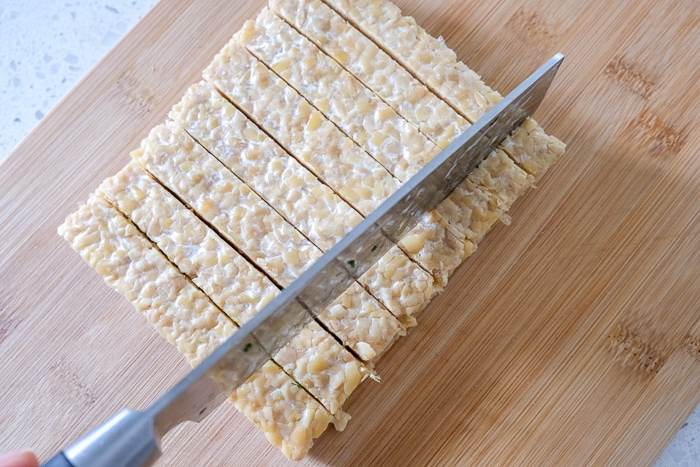 brick of tempeh being cut with large knife on wooden board