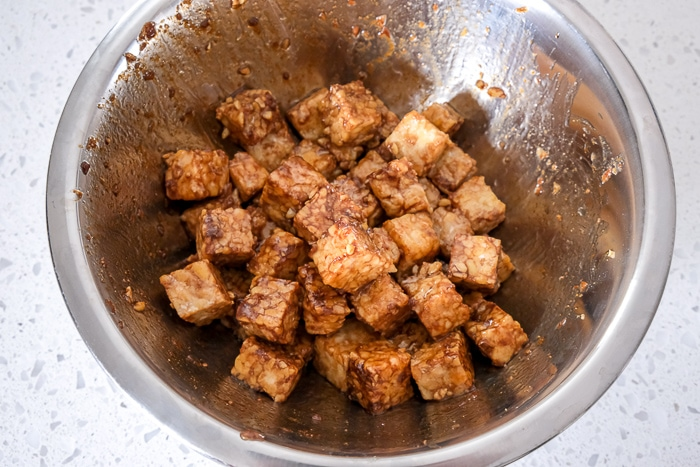 pieces of marinated tempeh in silver mixing bowl on white counter