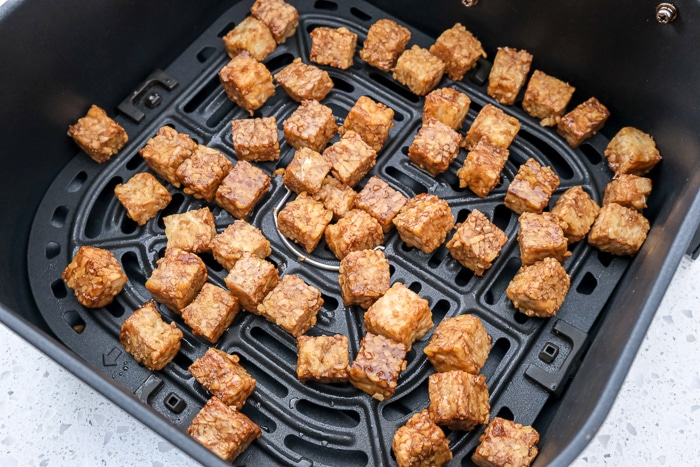 pieces of tempeh in black are fryer tray on white counter
