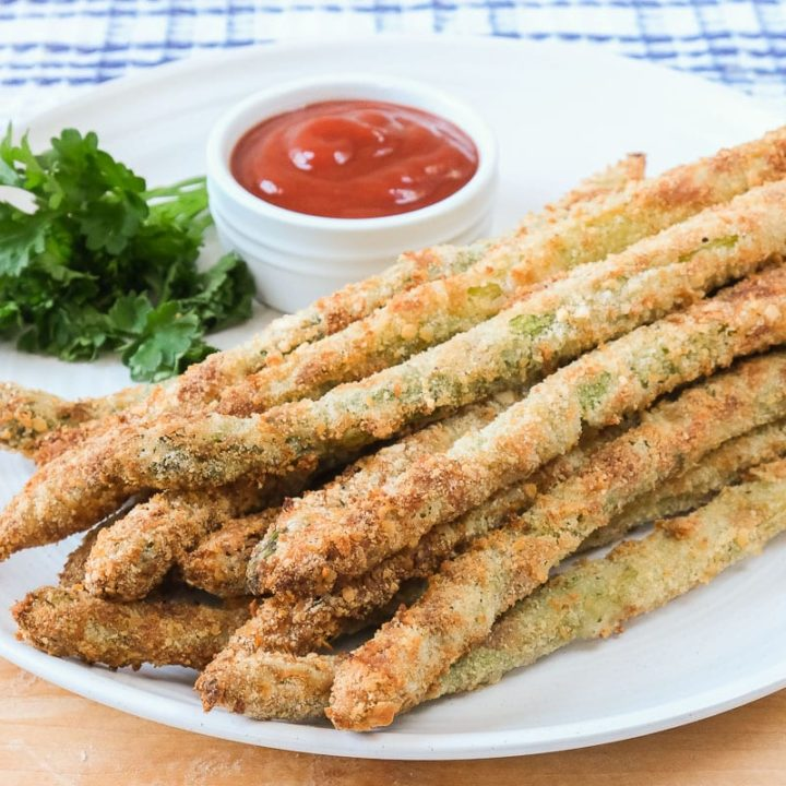 breaded asparagus fries on white plate with ketchup and parsley behind