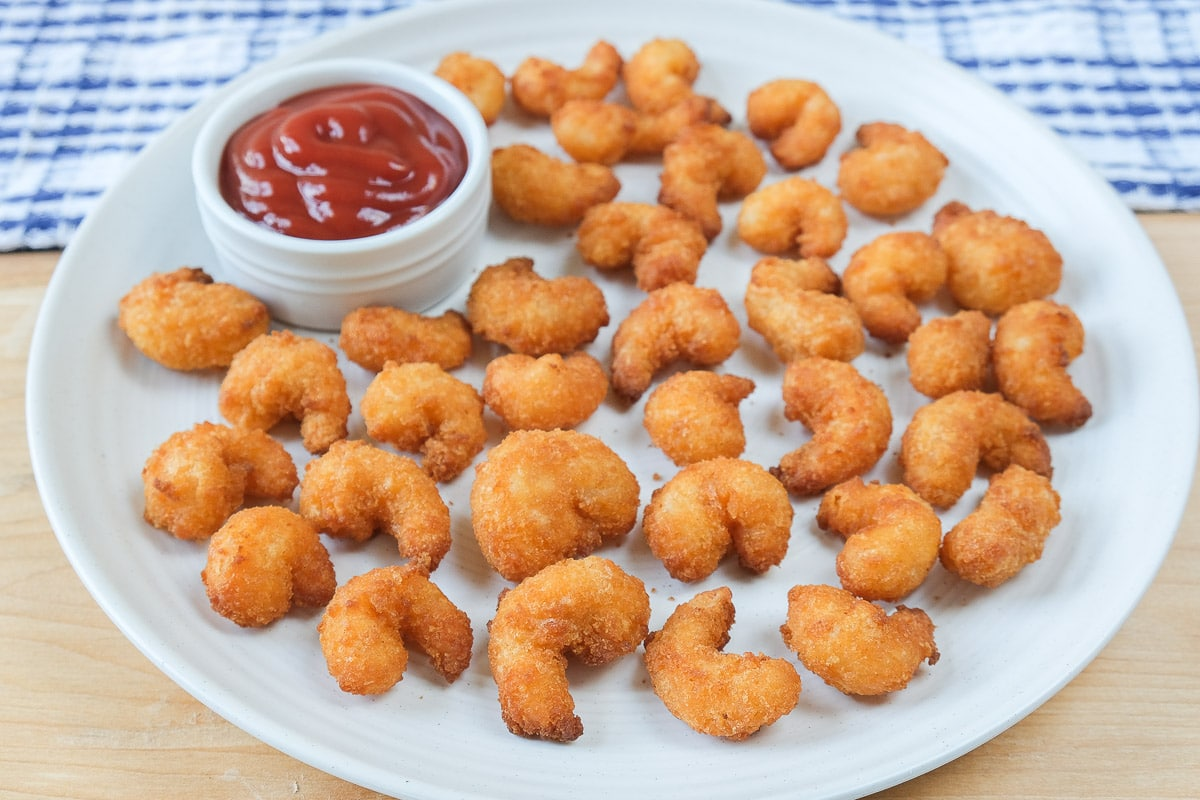popcorn shrimp on plate with ketchup for dipping behind