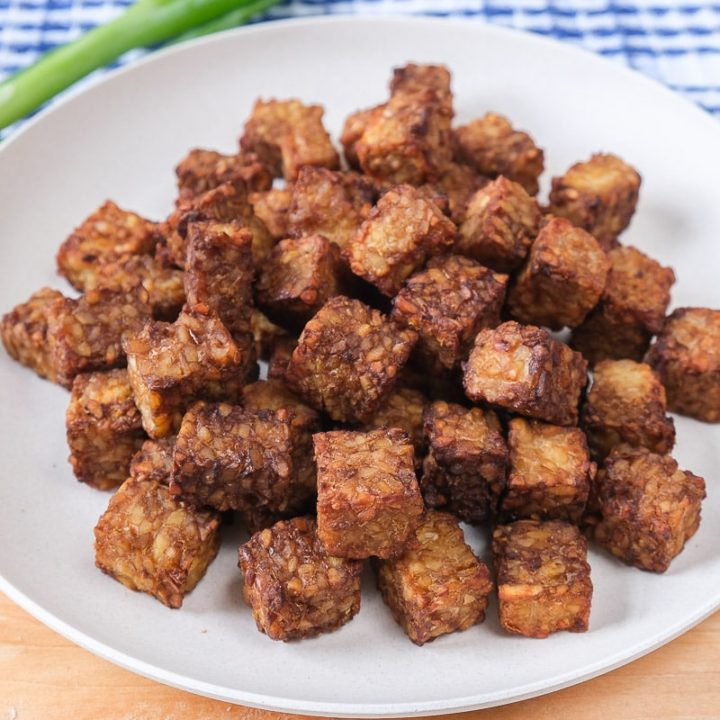 white plate of tempeh cubes on wooden board